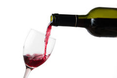 Pour red wine in glass. On white background Royalty Free Stock Image