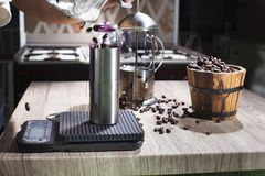 Pour the roasted coffee beans into the manual coffee bean grinding machine. royalty free stock photos