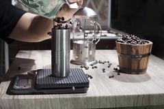 Pour roasted coffee beans into a manual coffee grinder. stock photo