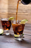 Pour the rum and cola cuba libre with lime, ice Royalty Free Stock Image