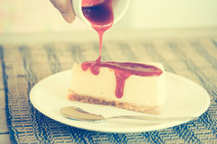 Pour sauce into cheesecake Royalty Free Stock Image