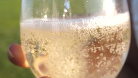 Pour sparkling wine from a bottle into transparent glasses. close-up. champagne sparkles and foams in the sun. Slow. Motion. teamwork of loving couple stock footage