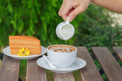 Pour syrup in a cup of coffee. Stock Image