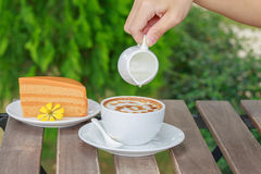 Pour syrup in a cup of coffee. Stock Photos