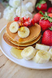 Pour syrup on stack of pancake with strawberry and slice of bana Stock Images