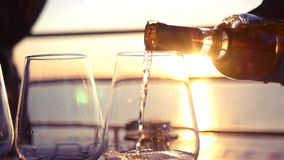 Pour tasty white wine at sunset by the sea. HD, 1920x1080. slow motion