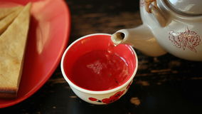 Pour tea into a bowl from teapot stock footage