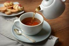 Pour the tea into the cup. Closeup Royalty Free Stock Photos