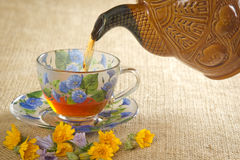 Pour the tea into a mug from the kettle stock images
