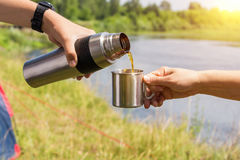 Pour the tea from the thermos into a mug . Pour the tea from the thermos into a mug on the background of the river stock photography
