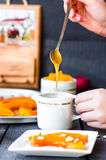 Pour a teaspoon honey in ceramic ware, baked pumpkin, hands Royalty Free Stock Images