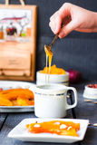 Pour a teaspoon honey in ceramic ware, baked pumpkin Stock Photos