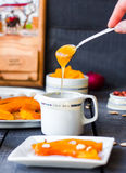Pour a teaspoon honey in ceramic ware, baked pumpkin Royalty Free Stock Photo