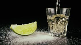 Pour tequila in a shot. Slow motion. Salt on a table with a lime slice about pour to a shot a tequila. Slow motion stock video footage