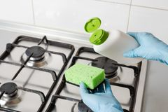 Pour washing detergent from bottle to green sponge. Cleaning gas stainless kitchen stove with effective soap liquid in blue rubber gloves. Pouring washing royalty free stock photo