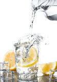 Pour water in glass with lemon Stock Images