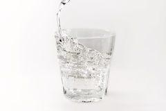 Pour water into a glass with splashes on a white background Royalty Free Stock Photography
