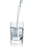 Pour water into the half-full glass with reflection isolated on. White background Stock Photo