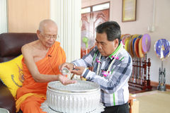 Pour water on the hands of Lord Abbot of Buddhist Monastery. Trang, Thailand - April 13, 2016: Trang Governor Mr.Dejrath Simsiri pour water on the hands of Lord Stock Photo