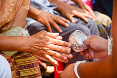 Pour water on the hands of revered elders and ask royalty free stock photo