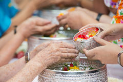 Pour water on the hands of revered elders and gives blessing in Stock Image