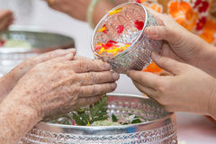 Pour water on the hands of revered elders and gives blessing in Royalty Free Stock Image
