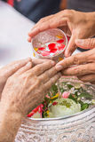 Pour water on the hands of revered elders and gives blessing in Stock Photography