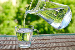 Pour water from a jug into a glass. Outdoors in summer Royalty Free Stock Photos