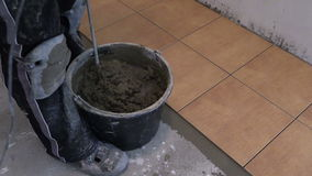 Pour water on mixture in bucket and mix tile adhesive glue stock footage