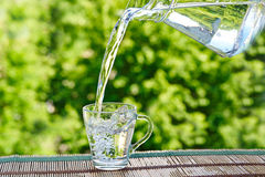 Pour water from pitcher into glass. On green background Royalty Free Stock Image