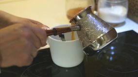 Pour in a white cup of coffee cooked in a bowl. 4k, 3840x2160. HD stock video footage