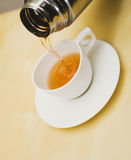 Pour a white cup of tea from thermos Royalty Free Stock Image