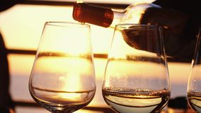 Pouring white wine in four glasses at amazing sunset by the sea in beach cafe before partying in slow motion. 3840x2160