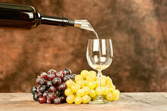 Pour wine in cup. Pour wine from bottle in shiny wine cup near grape Royalty Free Stock Photos
