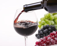 Pour the wine into a glass. Pour the red wine into a glass and  grape Stock Photo