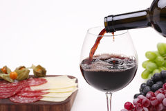 Pour the wine into a glass. Pour the red wine into a glass and  grape, cheese, meat Royalty Free Stock Photo