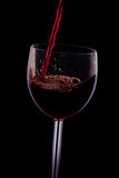 Pour the wine into the glass on a black background. Pour the wine into a transparent glass on a black background Stock Photos