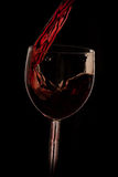 Pour the wine into the glass on a black background Royalty Free Stock Image