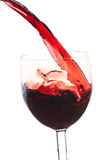 Pour the wine into the glass on a white background. Pour the wine into a transparent glass on a white background Stock Photos