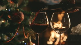 Pour the wine into the glasses on the background of the Christmas tree and fireplace stock video footage