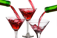 Pour the wine into the glasses on a white background.  Stock Images