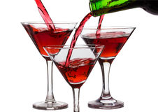 Pour the wine into the glasses on a white background.  Royalty Free Stock Images