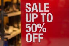 Pourcentage jusqu'à 50 rouge de vente de signe dans l'affichage de fenêtre de magasin photographie stock
