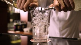 Poured alcohol in a glass with ice. Bartender pours alcohol from 2 bottles into a glass full of ice on the bar counter stock video