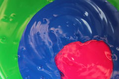 Poured Paint. Red, blue, & green paint poured on top of each other Royalty Free Stock Image