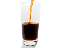 Poured Soft Drink. Soft drink being poured in to glass with some bubbles forming at the break. with a shadow at the bottom of the glass Stock Image