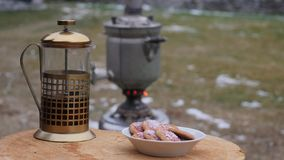Poured tea in a mug in the backyard during the cold season. big old samovar. 4K stock video footage