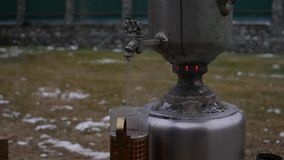 Poured tea in a mug in the backyard during the cold season. big old samovar. slow motion stock footage