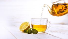Poured from a teapot cup of tea and lemon and mint on a wooden t. Able royalty free stock photos