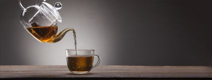 Poured from a teapot. Cup of tea on a wooden table Royalty Free Stock Image